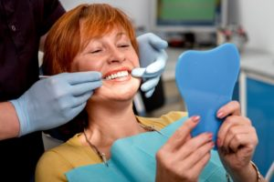 A woman examines her new teeth.